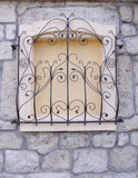 Decorative wrought iron grille on walled window Stock Images