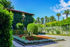 Decoratively trimmed bushes located on the background of the house. Beautiful places of the Nikitsky Botanical Garden, Yalta Crimea Royalty Free Stock Photography