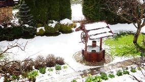 Decorativo bien en el patio trasero en un día nevoso de la primavera temprana metrajes