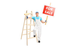 Decorator holding paint roller and a for sale sign Stock Photo