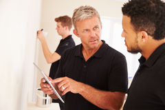 Decorator instructing colleague painting a room Stock Photography