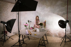 Decorator make flower bouquet at studio. Young girl makes an ornament from white flowers in a workshop. Photoshoot backstage Stock Image