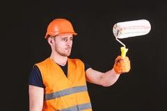 Decorator obrazu powierzchnia przed on Mężczyzna w hełmie, ciężki kapelusz trzyma farba rolownika, czarny tło Farba i obraz royalty free