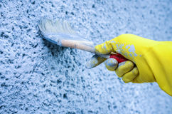 Decorator painting wall with blue paint. Hand in glove with a paint brush painting on wall Royalty Free Stock Images