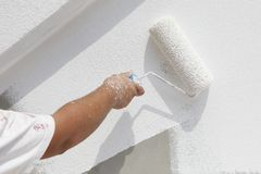 Decorator painting wall. Hand of a decorator painting a white wall with a roller Stock Photography