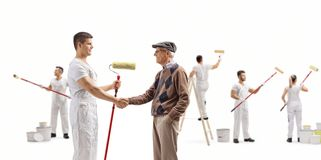 Decorator with a roller painter shaking hands with a senior and people painting wall. Full length shot of a decorator with a roller painter shaking hands with a royalty free stock photo