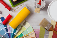 Decorator's work table with tools. Painter and decorator work table with house project, color swatches, painting roller and paint brushes, top view Royalty Free Stock Photo