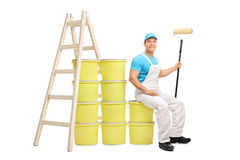 Decorator sitting on a pile of color buckets. Young male decorator sitting on a pile of color buckets next to a wooden ladder isolated on white background Royalty Free Stock Photo