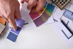 Decoratore che mostra un tono di colore sulla vista del piano d'appoggio del lavoro Fotografia Stock Libera da Diritti