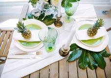 Decorazione con colori verdi e bianchi degli ananas, dei piatti, delle candele, Fotografie Stock