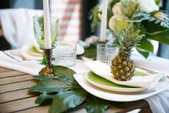 Decorazione con colori verdi e bianchi degli ananas, dei piatti, delle candele, Fotografia Stock Libera da Diritti
