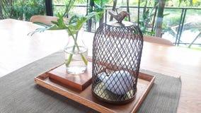 Decorazione d'annata di stile con ed uccello ceramico in gabbie con il vaso sulla tavola immagini stock libere da diritti