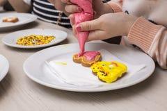 Decorazione dei biscotti dalle bambine fotografie stock libere da diritti