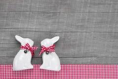 Decorazione dei conigli di Pasqua nell'interno su un fondo di legno dentro Immagini Stock