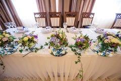 Decorazione dei fiori sulla sposa e sullo sposo della tavola di nozze fotografia stock