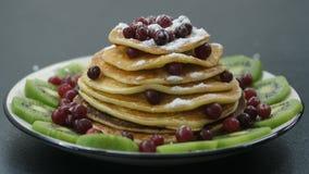 Decorazione dei pancake con la bacca e lo zucchero in polvere video d archivio
