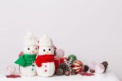 Decorazione dei pupazzi di neve con il contenitore di regalo rosso Fotografie Stock