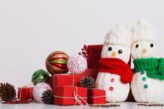 Decorazione dei pupazzi di neve con il contenitore di regalo rosso Fotografie Stock Libere da Diritti