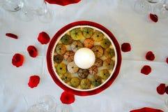 Decorazione del centro tavola nel rosso con le coperture ed i petali del riccio di mare Immagine Stock