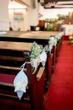 Decorazione del fiore bianco lungo il banco di chiesa su tappeto rosso in cristiano fotografia stock libera da diritti
