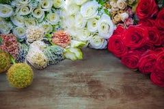 Decorazione del mazzo di bianco, delle rose rosse e dei fiori sopra la tavola di legno Fotografia Stock