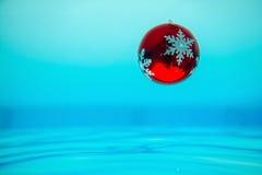 Decorazione dell'albero del nuovo anno che entra nell'acqua blu Fotografia Stock