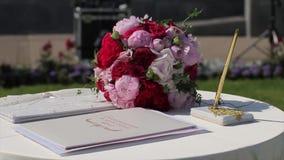 Decorazione dell'arco di nozze con la tavola di registrazione per le persone appena sposate con i fiori viola e porpora Il sole s stock footage
