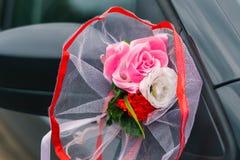 Decorazione dell'automobile di nozze, specchietto retrovisore e fiori artificiali fotografia stock