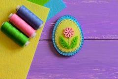 Decorazione dell'uovo di Pasqua del feltro di giallo e del blu con il fiore rosa Mestieri adorabili di Pasqua per i bambini Picco Fotografia Stock Libera da Diritti