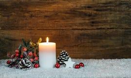 Decorazione della candela di Natale con la pigna, l'albero di abete, le bacche rosse, la stella e le bagattelle rosse di natale Fotografia Stock