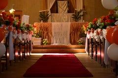 Decorazione della chiesa sul giorno delle nozze con i fiori e gli impulsi e un tappeto rosso nel tema arancio ed i raggi di sole  immagine stock libera da diritti