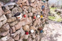 Decorazione della parete di pietra del giardino con le tazze del ferro, utensili del ferro con i fiori Giorno pieno di sole fotografia stock libera da diritti