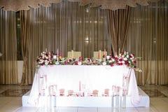 Decorazione della tavola di nozze con i fiori e le candele rossi Fotografia Stock