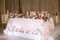 Decorazione della tavola di nozze con i fiori e le candele rossi Fotografie Stock