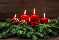 Decorazione di arrivo con quattro candele brucianti rosse Fotografie Stock Libere da Diritti
