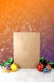Decorazione di carta di natale dei sacchetti della spesa con le palle e le stelle sul fondo dell'annata del bokeh della neve Fotografie Stock