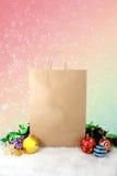 Decorazione di carta di natale dei sacchetti della spesa con le palle e le stelle sul fondo dell'annata del bokeh della neve Fotografia Stock