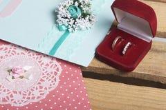 Decorazione di cerimonia nuziale Carte di IInvitation e fedi nuziali in una scatola, bugia su una scatola di legno Fotografie Stock