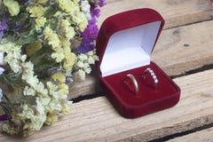 Decorazione di cerimonia nuziale Le fedi nuziali in scatola si trovano su una scatola di legno Un mazzo dei fiori secchi vicino Fotografia Stock Libera da Diritti
