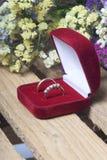 Decorazione di cerimonia nuziale Le fedi nuziali in scatola si trovano su una scatola di legno Un mazzo dei fiori secchi vicino Fotografie Stock