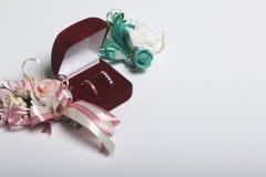 Decorazione di cerimonia nuziale Sposo di Boutonniere con la sposa, le loro fedi nuziali in scatola, bugia su una superficie bian Fotografia Stock