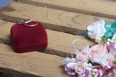Decorazione di cerimonia nuziale Sposo di Boutonniere con la sposa, le loro fedi nuziali sulla scatola, bugia su una scatola di l Immagine Stock