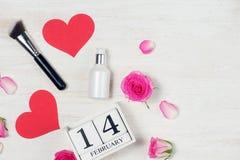 Decorazione di giorno del ` s del biglietto di S. Valentino con i fiori ed il blocchetto di calendario rosa Fotografia Stock