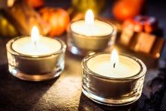 Decorazione di Halloween con tre luci, cioccolato e zucche del tè sull'ardesia Fotografia Stock