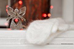 Decorazione di legno sveglia di angelo sull'albero di Natale e guanti tricottati bianchi sui precedenti delle luci rosse sulla vi immagini stock