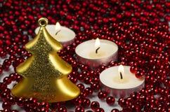 Decorazione di Natale - albero di vetro dell'oro e 3 canldes con la catena Fotografia Stock