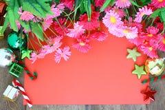 Decorazione di Natale, carta rossa e fiore su fondo di legno Fotografie Stock