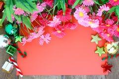 Decorazione di Natale, carta rossa e fiore su fondo di legno Immagine Stock