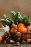 Decorazione di natale con i mandarini ed i dadi con copyspace su woode Immagine Stock