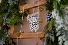 Decorazione di Natale con il cono, l'albero di abete e le scale Fotografie Stock